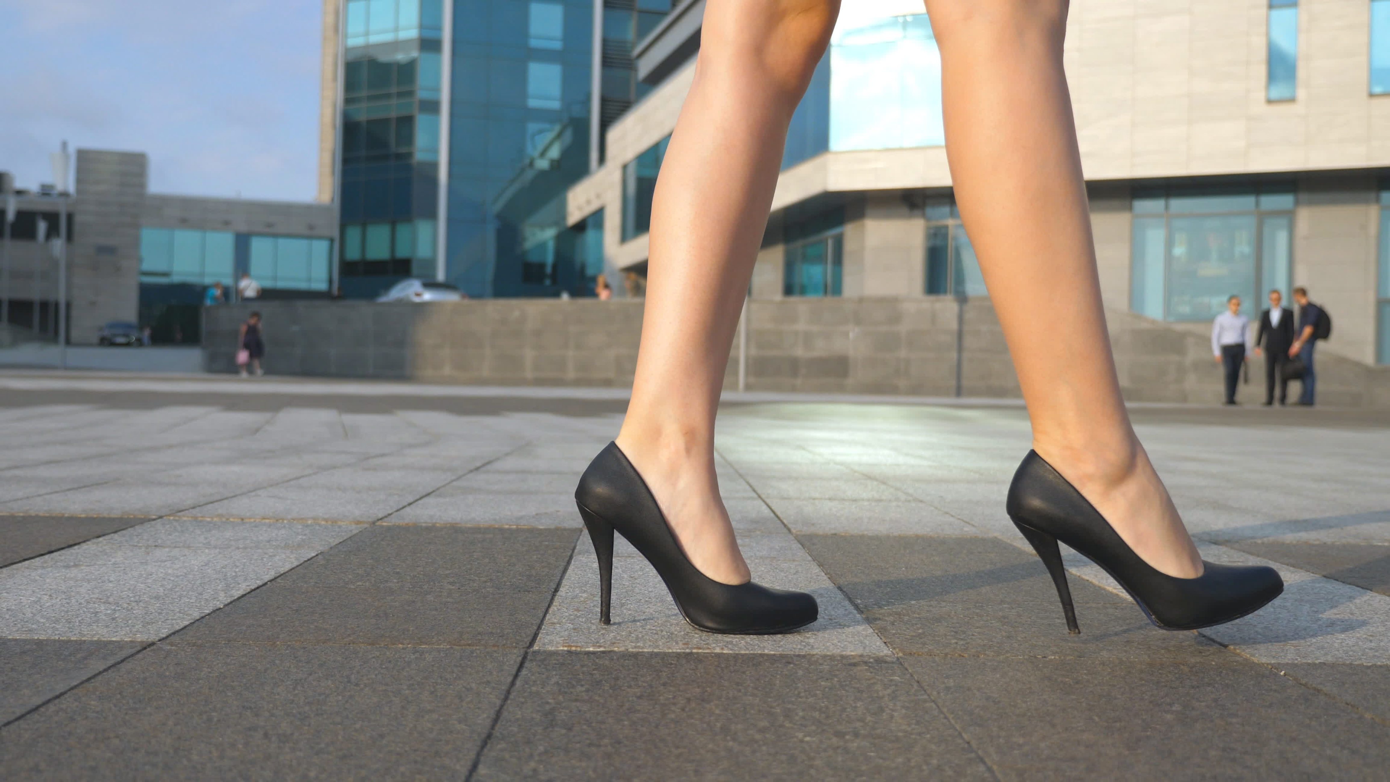 Female legs in high heels shoes walking in the urban street. Feet of young business woman in high-heeled footwear going in the city. Girl stepping to work. Slow motion Close up.